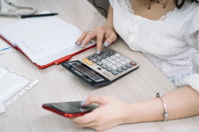 Woman using calculator for loan analysis.